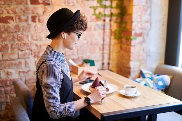 Jovem mulher elegante com airpods sentado no café no intervalo do almoço e comendo sobremesa deliciosa por tabela