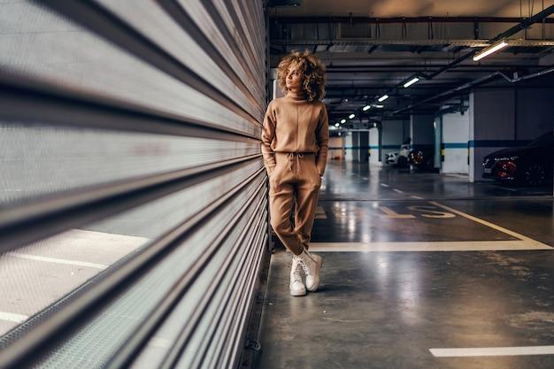 Jovem mulher elegante com cabelo encaracolado, de mãos dadas nos bolsos em pé na garagem subterrânea.