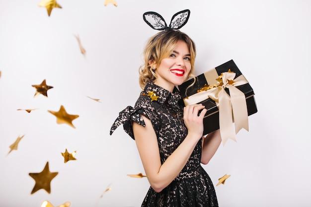 Jovem mulher elegante com caixa de presente, comemorando, usando vestido preto e coroa preta, feliz aniversário, confete de ouro cintilante, se divertindo.