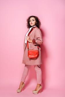 Jovem mulher elegante com casaco rosa na moda