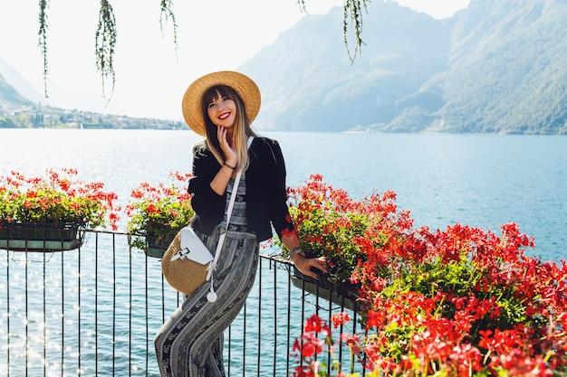 Jovem mulher elegante com chapéu de palha em uma varanda com flores no lago de como
