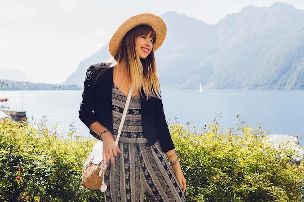 Jovem mulher elegante com chapéu de palha no lago de como