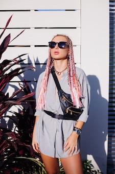Jovem mulher elegante com tranças rosa roxas e bolsa preta na cintura posando ao ar livre