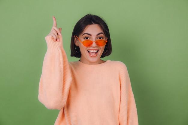 Jovem mulher elegante com um suéter casual cor de pêssego e óculos laranja isolados em uma parede verde oliva animada aponta o dedo indicador para cima do espaço da cópia