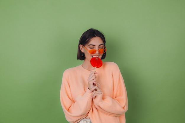 Jovem mulher elegante com um suéter casual cor de pêssego e óculos laranja isolados em uma parede verde oliva com um pirulito laranja sorriso positivo e espaço de cópia
