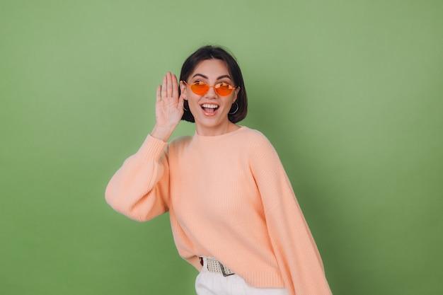 Jovem mulher elegante com um suéter casual cor de pêssego e óculos laranja isolados em uma parede verde oliva, curiosa, tentando ouvir o que você está dizendo com a mão na orelha, copie o espaço