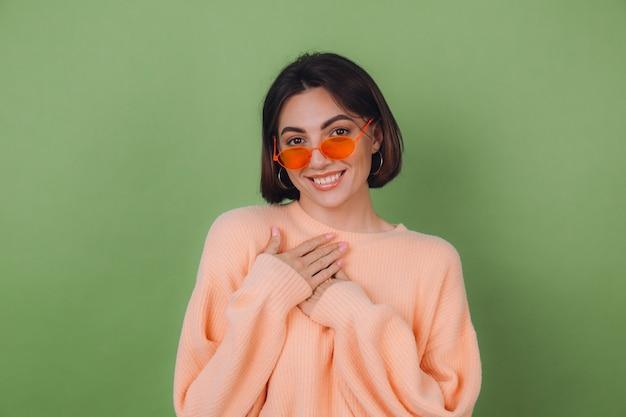 Jovem mulher elegante com um suéter casual cor de pêssego e óculos laranja, isolados na parede verde-oliva positiva, de mãos dadas sobre o peito
