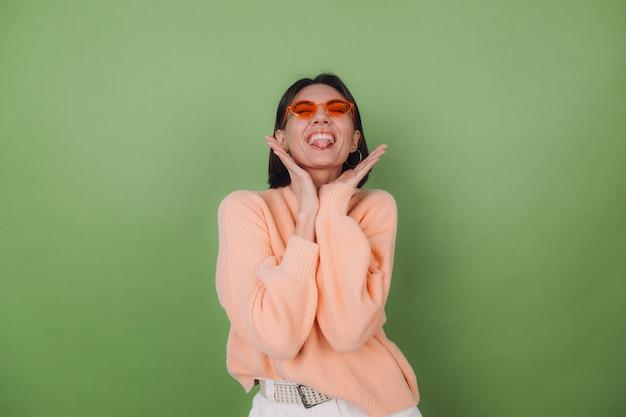 Jovem mulher elegante com um suéter casual cor de pêssego e óculos laranja, isolados na parede verde oliva.
