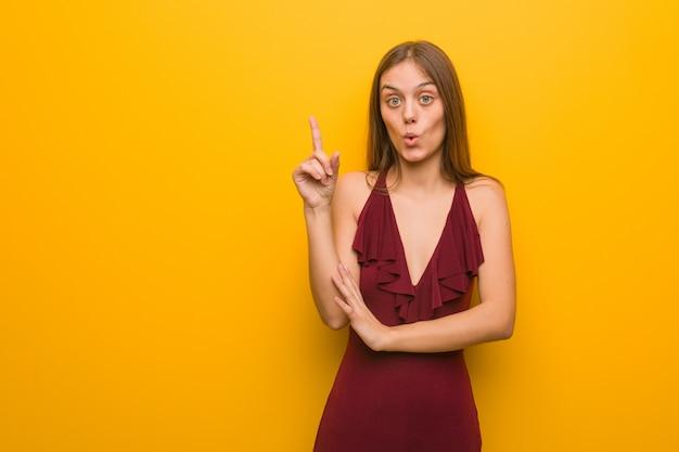Jovem mulher elegante com um vestido, tendo uma ótima idéia