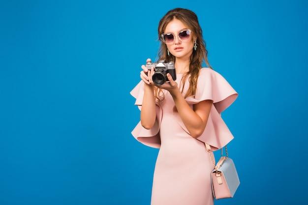 Jovem mulher elegante com vestido rosa luxuoso tirando fotos com a câmera vintage