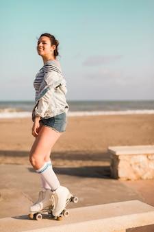 Jovem mulher elegante de sorriso que está no banco na praia