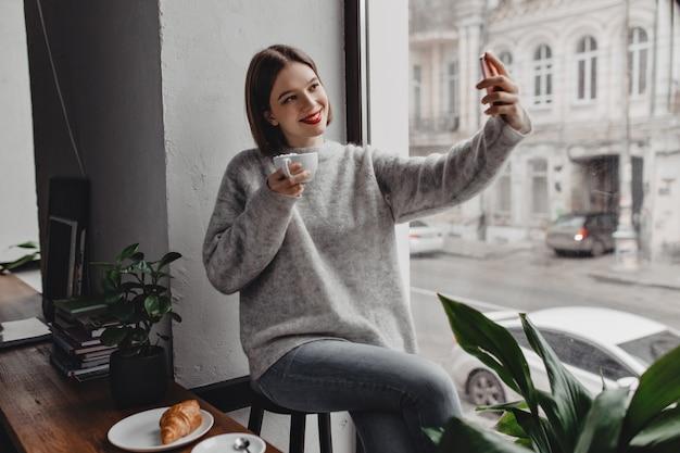 Jovem mulher elegante de suéter cinza e calça jeans posando com uma xícara de cappuccino e tomando selfie pela janela.
