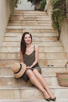 Jovem mulher elegante e atraente em um vestido elegante, sentada na escada, chapéu e bolsa de palha, estilo verão, tendência da moda, férias, sorrindo, acessórios elegantes, óculos de sol, posando em uma vila tropical em bali
