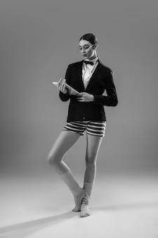 Jovem mulher elegante e elegante usando jaqueta e meias trabalhando em casa, durante o isolamento.