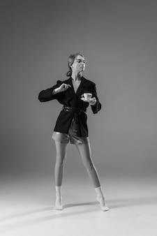 Jovem mulher elegante e elegante, vestindo jaqueta e meias, trabalhando em casa.