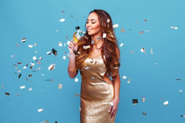 Jovem mulher elegante em maquiagem de noite de vestido glitter dourado segurando uma taça de champanhe e celebrat ...