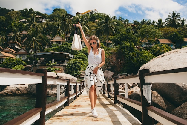 Jovem mulher elegante em pé no cais, caminhando, ouvindo música em fones de ouvido, roupas de verão, saia branca, bolsa, água azul, plano de fundo de paisagem, lagoa tropical, férias, viajando na ásia