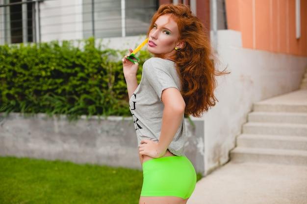Jovem mulher elegante em roupas de ginástica, cabelo ruivo, shorts verdes, óculos escuros, camiseta grande, ressaca, clima de festa. se divertindo, sexy, quente, sedutor, corpo esguio, atlético,