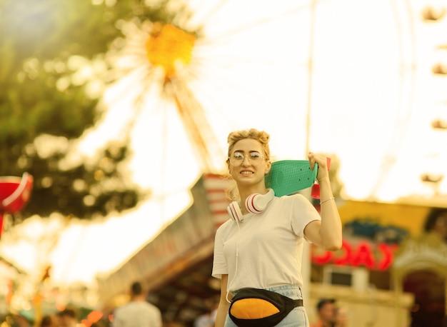 Jovem mulher elegante em roupas elegantes de juventude com um skate nos ombros e se divertindo em um parque de diversões