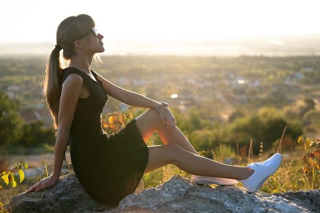 Jovem mulher elegante em um vestido preto curto e tênis branco, sentado em uma rocha relaxante ao ar livre em noite de verão. senhora elegante, apreciando o pôr do sol quente na natureza.