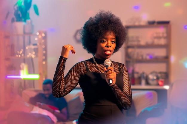 Jovem mulher elegante em um vestido preto elegante cantando karaokê no microfone no fundo de amigos no sofá em uma festa em casa