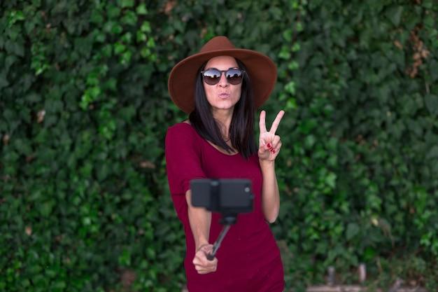 Jovem mulher elegante fazendo selfie sobre hera verde folhas fundo, vestindo chapéu marrom elegante, camiseta vermelha e óculos de sol, fazendo selfie e se divertindo.