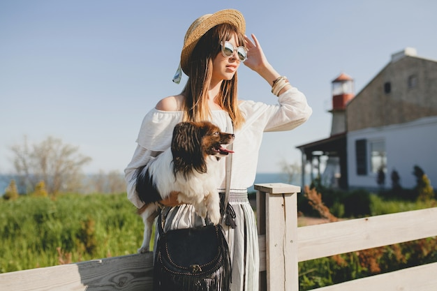 Jovem mulher elegante no campo, segurando um cachorro, feliz humor positivo, verão, chapéu de palha, roupa de estilo boêmio, óculos de sol, sorrindo, feliz, ensolarado