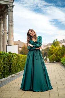 Jovem mulher elegante relaxando e posando para a câmera perto de colunas com um vestido verde em um dia perfeito de verão.