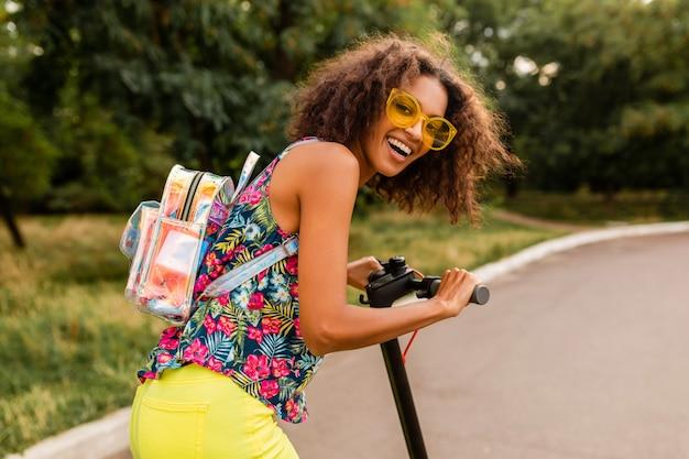 Jovem mulher elegante se divertindo no parque, andando de scooter elétrica
