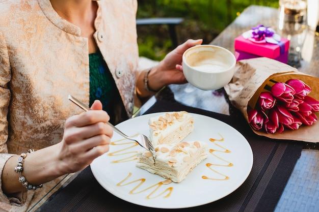 Jovem mulher elegante sentada em um café, segurando uma xícara de cappuccino e comendo um bolo saboroso,