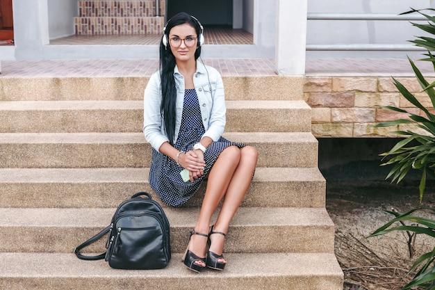 Jovem mulher elegante sentada na escada com smartphone, ouvindo música em fones de ouvido, mochila, sorrindo, feliz, humor positivo, férias de verão, estilo jeans vintage