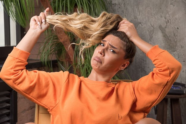 Jovem mulher elegante sentada na poltrona, fazendo o cabelo com uma expressão de dor.
