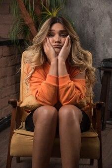 Jovem mulher elegante sentada na poltrona, segurando o rosto perto da parede.