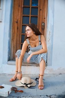 Jovem mulher elegante, sentado na porta na rua e sorrindo.