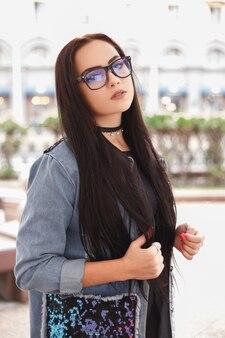 Jovem mulher elegante usando óculos pretos e jaqueta jeans azul