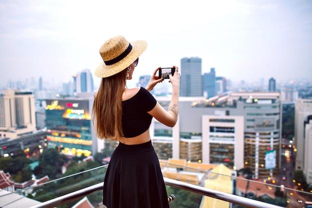 Jovem mulher elegante usando roupa de verão na moda, fazendo fotografia no terraço de um hotel de luxo