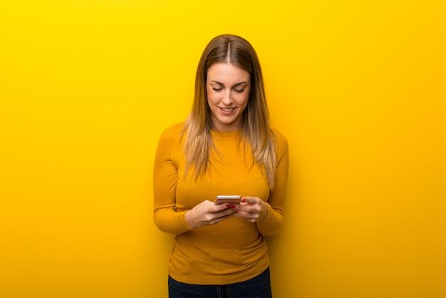 Jovem mulher em amarelo enviando uma mensagem com o celular