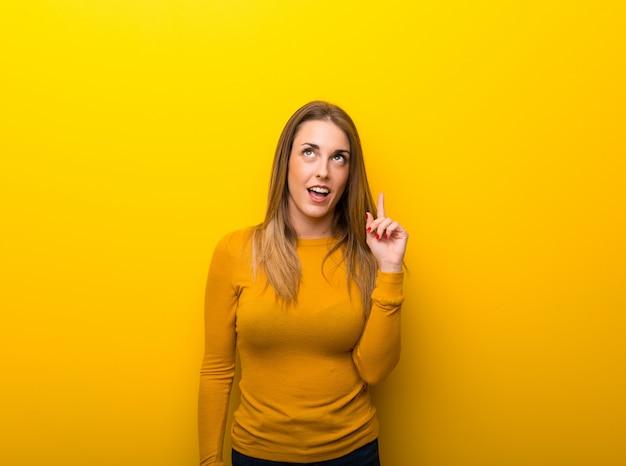 Jovem mulher em amarelo pensando uma ideia apontando o dedo para cima