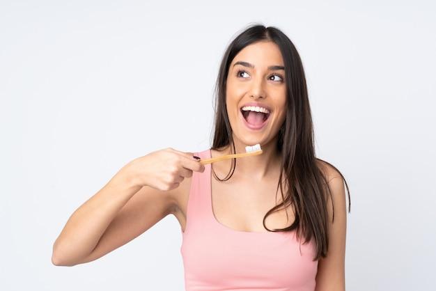 Jovem mulher em branco com uma escova de dentes