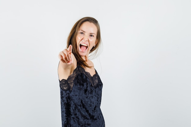 Jovem mulher em camiseta preta apontando para a câmera e parecendo louca