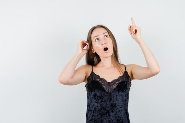 Jovem mulher em camiseta preta olhando para cima com o dedo para cima e parecendo surpresa