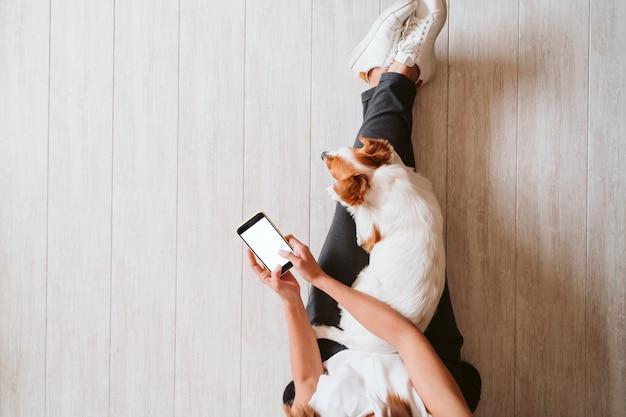 Jovem mulher em casa abraçando seu lindo cachorro pequeno