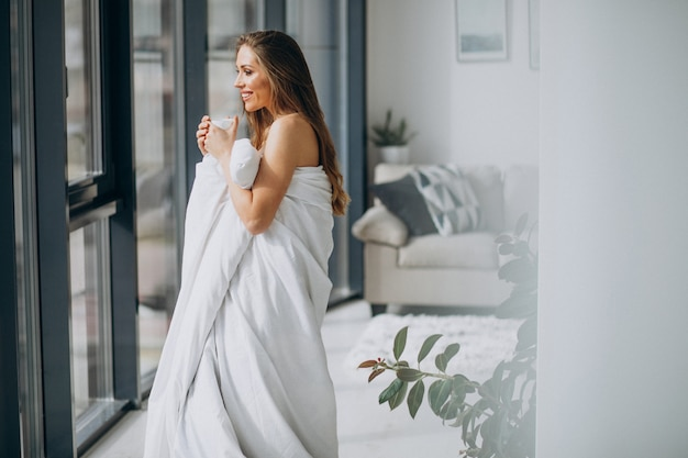 Jovem mulher em casa coberta no cobertor