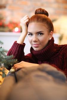 Jovem mulher em casa com decoração de natal
