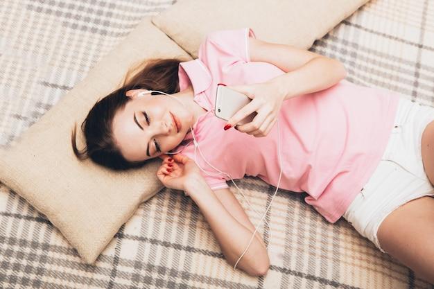 Jovem mulher em casa com o celular, surfando na internet em casa. tiro interno.