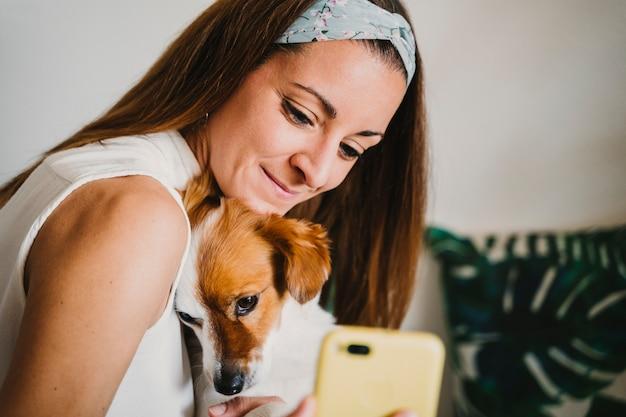 Jovem mulher em casa com seu lindo cachorro pequeno