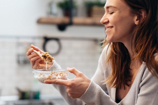 Jovem mulher em casa comendo granola na cozinha.
