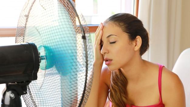Jovem mulher em casa num dia quente de verão na frente do ventilador de trabalho, sofrendo com o calor do verão.