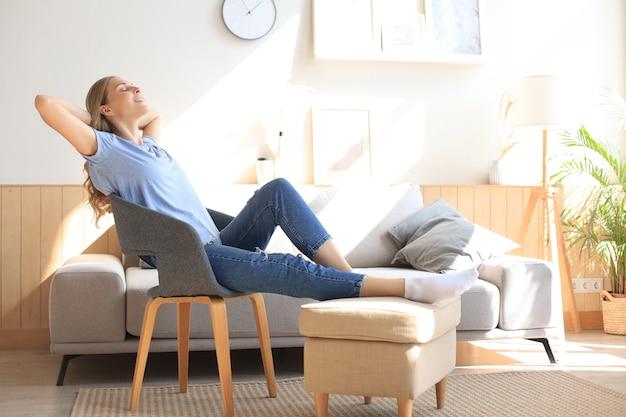 Jovem mulher em casa sentada na cadeira moderna em frente à janela, relaxando na sala de estar.