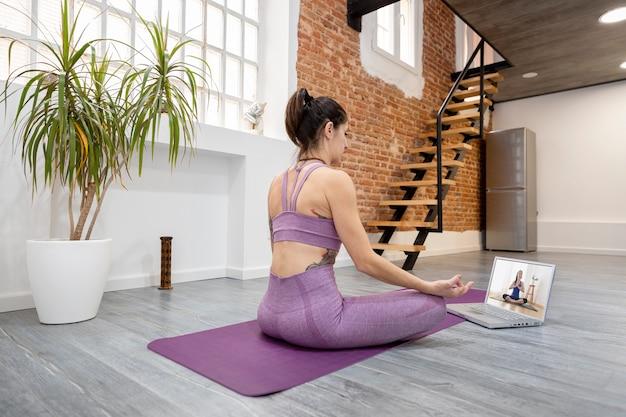 Jovem mulher em casa tendo uma aula de ioga online em seu laptop. bem-estar e conceito de novas tecnologias. espaço para texto.
